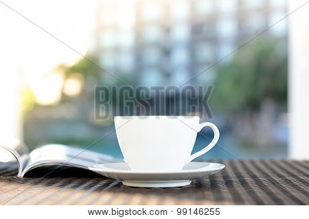 Coffee Cup With Book On The Table In Blurred Building & Green Plant Background - Chill Out In Resort