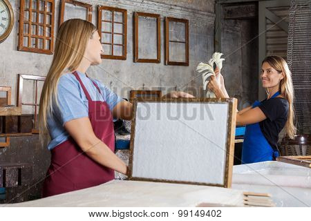 Happy mid adult female worker holding mold with paper while looking at colleague in factory