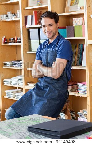 Portrait of smiling mid adult worker with arms crossed sitting in book store