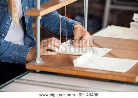 Midsection of female worker binding papers at workbench in factory