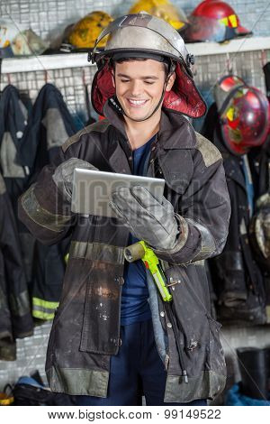 Happy fireman in uniform using digital tablet at fire station