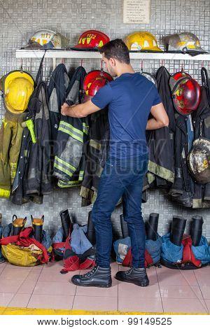 Full length of firefighter removing uniform hanging at fire station