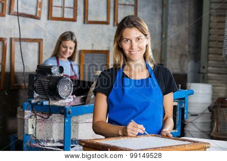 Portrait of confident female worker using tweezers to clean paper on mold in factory
