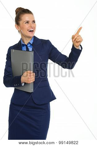Happy Businesswoman Holding File, Pointing Upwards, And Smiling