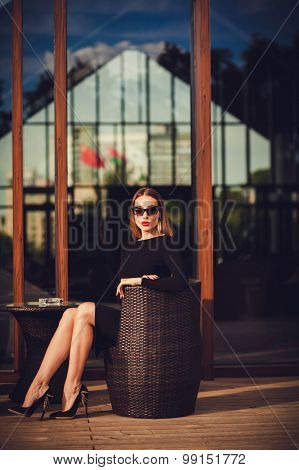 Young Woman In A Black Dress And Shoes In Cafe