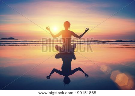 Silhouette young woman practicing yoga on the beach at surrealistic sunset. With the reflection in the wet sand.