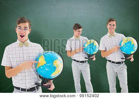 Nerd with globe against green chalkboard