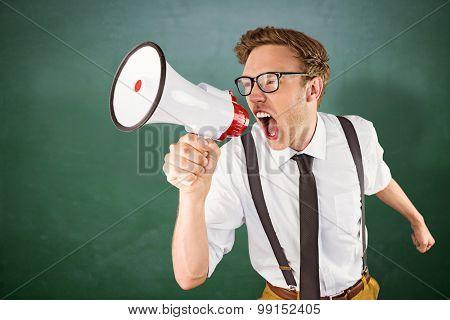 Geeky businessman shouting through megaphone against green chalkboard