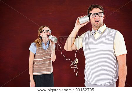 Geeky hipster couple speaking with tin can phone against desk