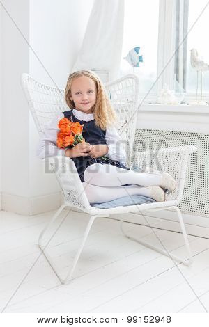 Female child sitting on the chair.