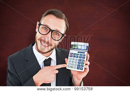 Geeky businessman pointing to calculator against desk