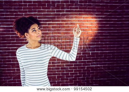 Young woman pointing the light on a red brick wall