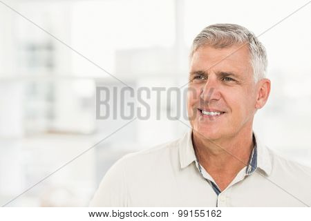 Close up view of a smiling businessman looking away in the office