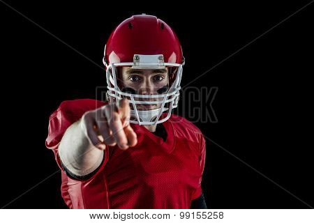 Portrait of american football player pointing to camera against black background