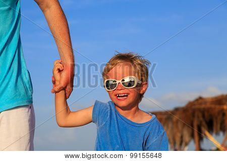 little boy having fun with dad on summer sky
