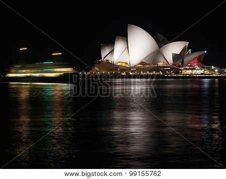 Sydney harbor with ferry light streaks and opera house by night from west side