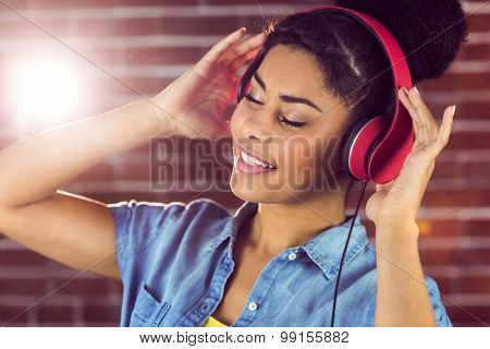 A smiling woman being transported by music on a brick wall