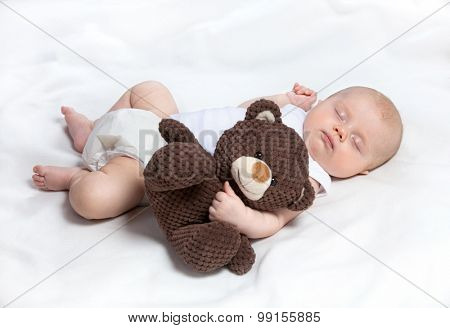 sweet sleeping baby girl holding hugging teddy bear lying down on white blanket caucasian studio shot