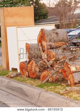 Large tree cutoffs and other items in front of middle class residential housing for the annual hard