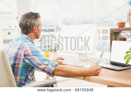 Casual designer editing photos with computer in the office
