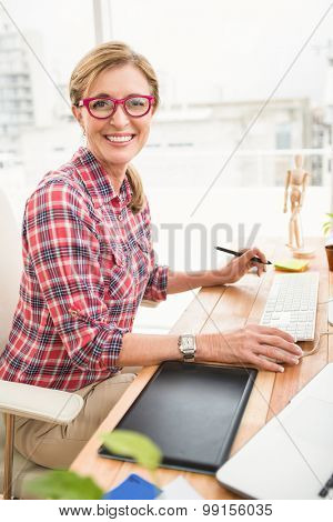 Portrait of smiling casual designer using computer in the office