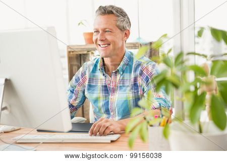Smiling casual designer working with computer in the office
