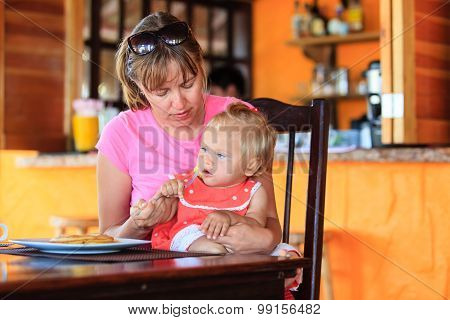 mother feeding little daughter in cafe