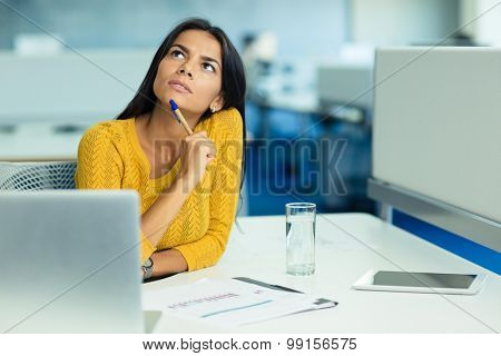 Portrait of a pensive businesswoman sitting at her workplace in office and looking up