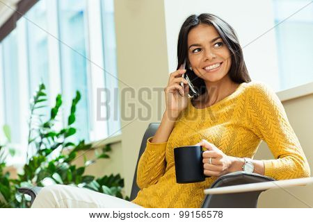 Portrait of a happy businesswoman talking on the phone and holding cup with coffee in office. Looking away