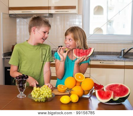 Healthy eating - children eating watermelon, lots of fresh fruit on the table in front.