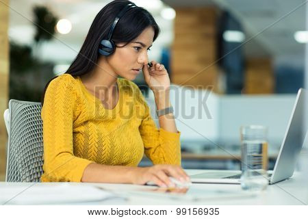 Portrait of a casual businesswoman in headphones using laptop in office