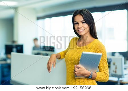 Portrait of a smiling cute businesswoman standing with tablet computer in office and looking at camera