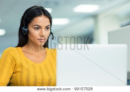 Portrait of a young businesswoman in headphones using laptop in office
