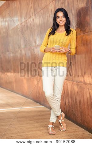 Full length portrait of a happy businesswoman standing with smartphone in hallway