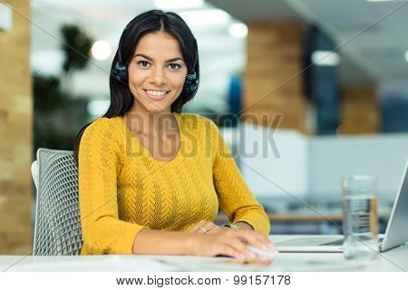 Portrait of a cheerful businesswoman in headphones sitting at her workplace in office and looking at camera