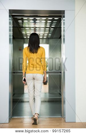 Back view portrait of a woman going in elevator indoors
