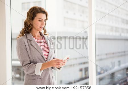 Casual businesswoman using smartphone in the office