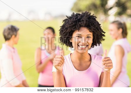 Portrait of smiling young woman wearing pink for breast cancer in front of friends in parkland