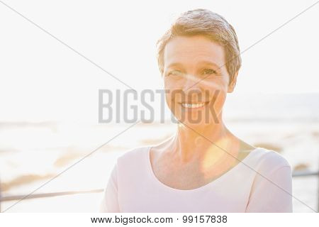 Portrait of smiling sporty woman at promenade on a sunny day