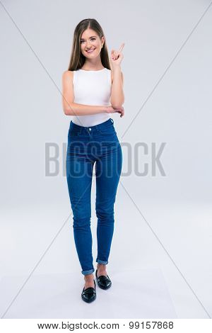 Full length portrait of a smiling female teenager pointing finger up isolated on a white background. Looking at camera