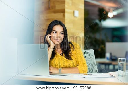 Portrait of a happy thoughtful businesswoman sitting at the table in office and looking away