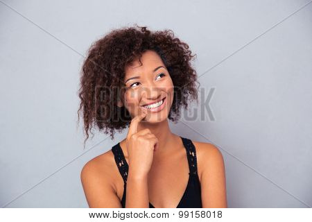 Portrait of happy thoughtful african woman looking up over gray background