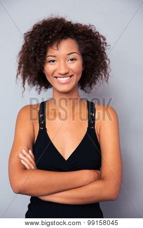 Smiling african woman standing with arms folded on gray background