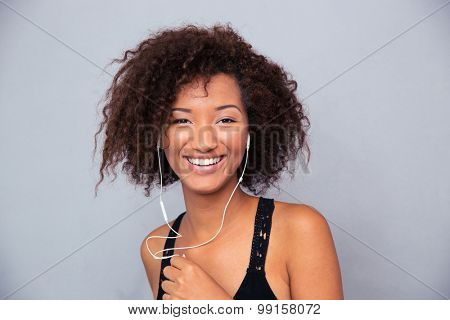 Portrait of a happy afro american woman listening music in headphones over gray background