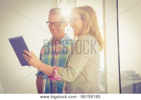 Smiling creative design team using tablet in the office