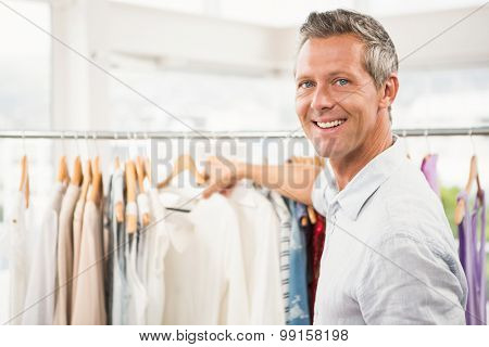 Portrait of smiling man browsing clothes in clothing store