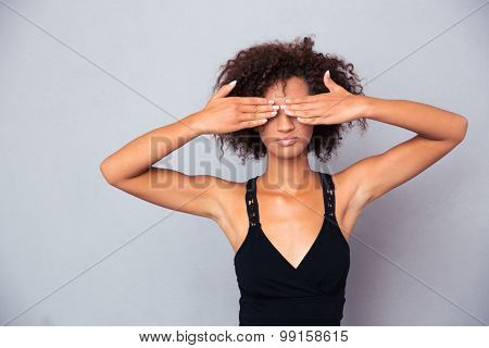Portrait of afro american woman covering her eyes over gray background