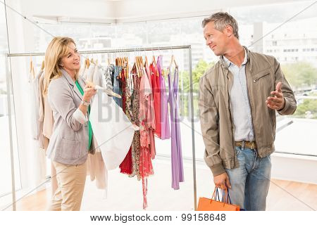 Smiling woman showing clothes to her man in clothing store