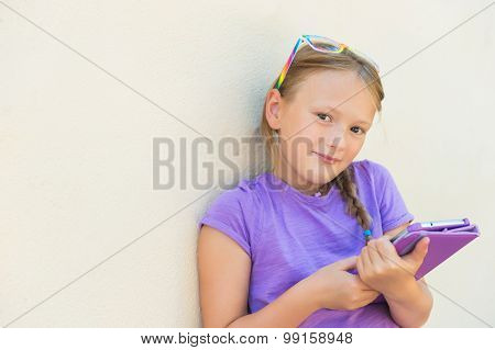 Adorable little girl playing on a digital tablet, wearing rainbow glasses