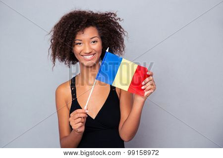 Portrait of a happy afro american woman holding Romanian flag over gray background and looking at camera